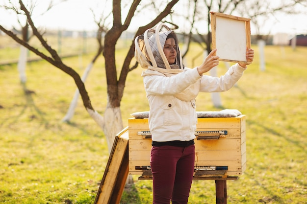 A young beekeeper girl is working with bees and beehives on the apiary