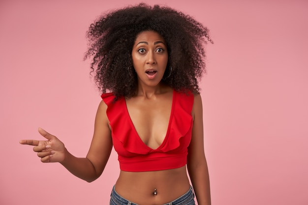 Young bemused dark skinned woman with belly button piercing pointing aside with forefinger while posing on pink with wde eyes and mouth opened