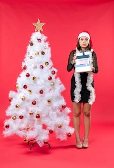 サンタクロースの帽子をかぶって、贈り物を持って誰かを指して飾られたクリスマスツリーの近くに立っている若い当惑した美しい女性