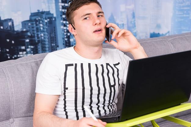 집에서 일하는 젊은 어리둥절한 남자는 소파에 앉아 메모를 작성하고 노트북 컴퓨터를 사용하는 동안 휴대 전화로 이야기하고 있습니다.
