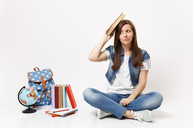 Young bewildered woman student in denim clothes holding book near head sitting near globe, backpack, school books isolated