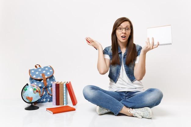 鉛筆を持って手を広げている眼鏡、地球の近くに座っているノートブック、バックパック、白い壁に隔離された教科書の若い当惑した女性学生