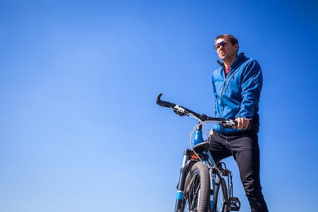 青空を背景に若い自転車