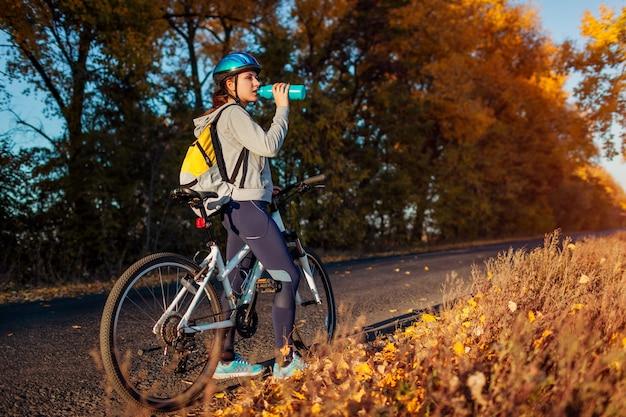 日没時に秋の畑に乗った後、休んでいる若い自転車乗り。道路で水を飲む女性。健康的な生活様式