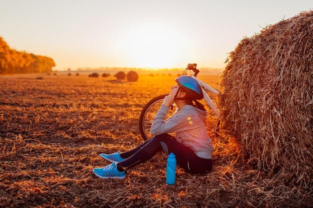日没時に秋の畑に乗った後、休んでいる若い自転車乗り。干し草の山のそばに座ってヘルメットを脱ぐ女性。スポーツレクリエーションの概念