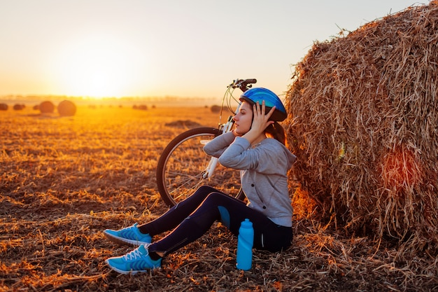 Young bicyclist having rest after a ride in autumn field at sunset. woman taking off helmet sitting by haystack