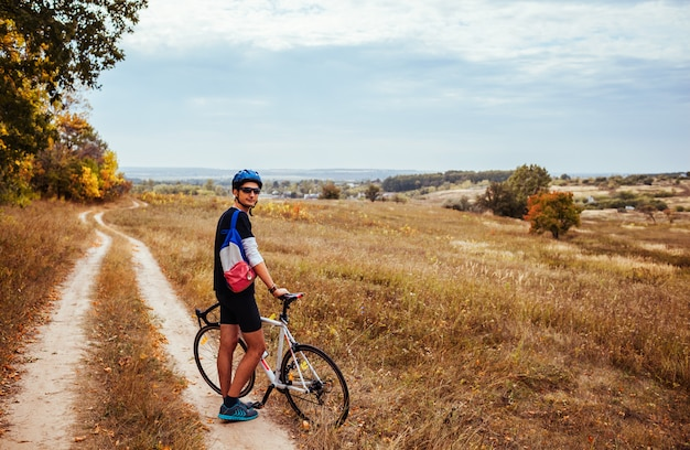 Young bicyclist  having rest in autumn field