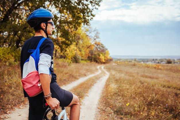 秋のフィールドで残りの部分を持つ若い自転車