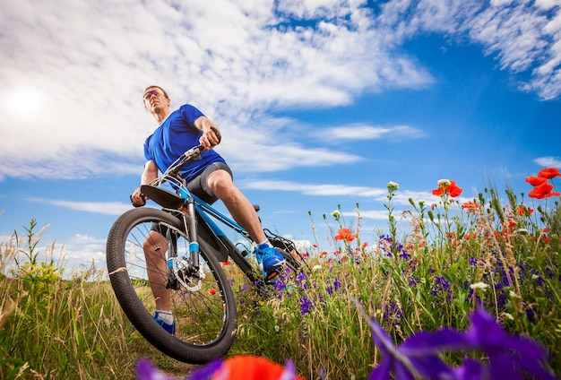 Young bicyclist rides on poppy field at sunset