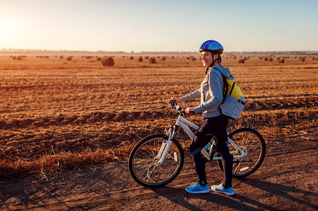 Young bicyclist riding in autumn field with haystacks at sunset, woman with backpack travelling,