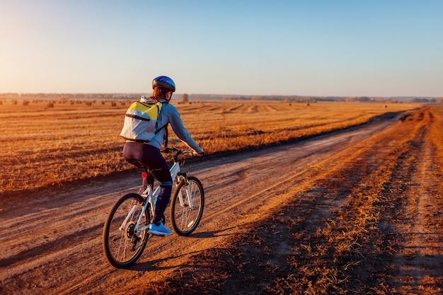 日没時に干し草の山と秋のフィールドに乗って若い自転車選手。自転車で旅行するバックパックを持つ女性。健康的な生活様式。