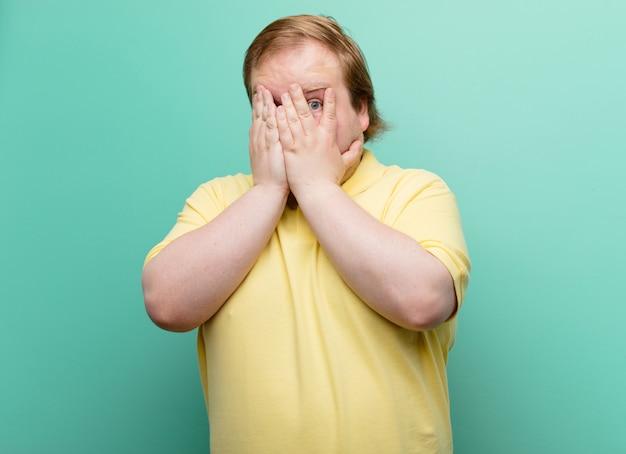 若いビッグサイズの男性の手で顔を覆っている、驚いた表情で指の間を覗いて、青い壁の側にいる