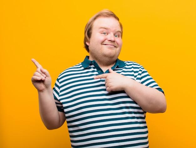 誇りに思って驚いた、自信を持って自分を指している、オレンジ色の壁で成功したナンバーワンのような感じの若いビッグサイズの男性