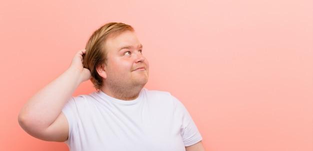 若いビッグサイズの男は困惑し、混乱し、頭をかいて、ピンクの壁の側面を見る