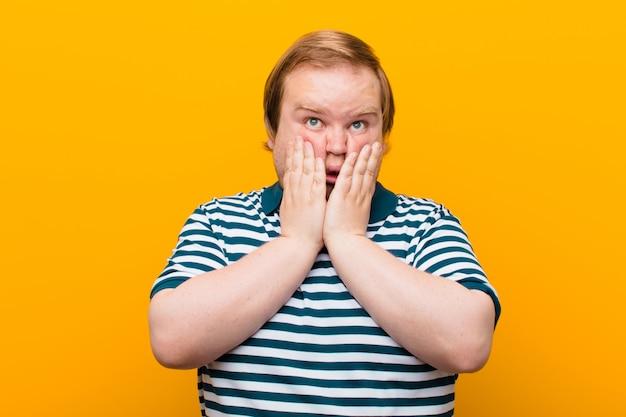 Молодой крупный мужчина выглядит глупо и смешно с глупым косоглазым выражением лица, шутит и дурачится у оранжевой стены