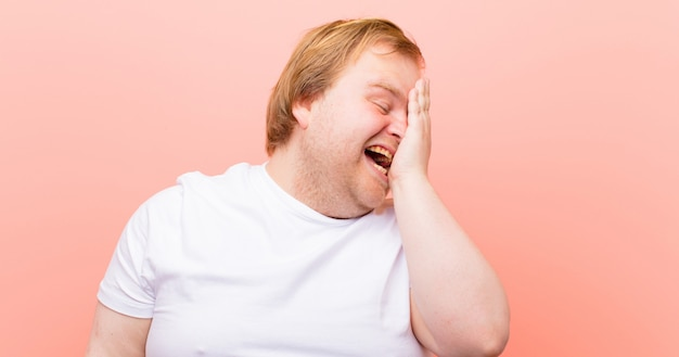 Young big size man looking sleepy, bored and yawning, with a headache and one hand covering half the face against pink wall