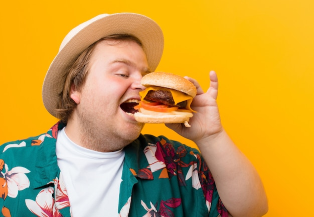 Young big size man with a cheese burger against flat wall