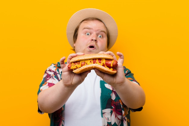 Young big size man with a hot dog against flat wall