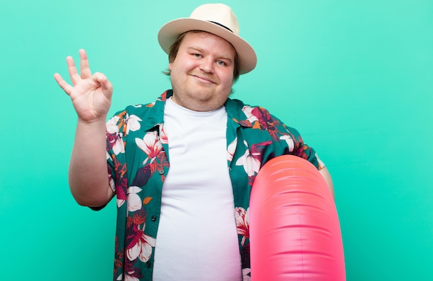 Young big size man with a inflatable donut against flat wall