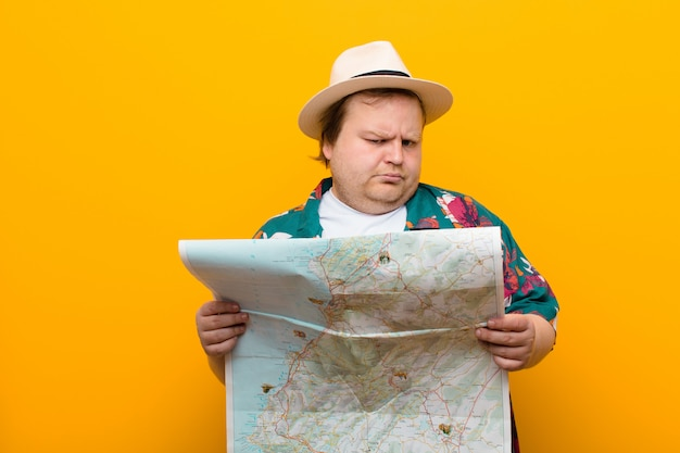 Young big size man with a map against flat wall