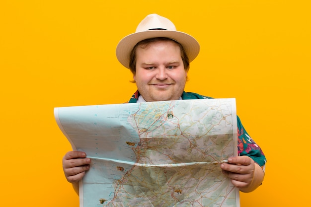 Young big size man with a map  flat wall