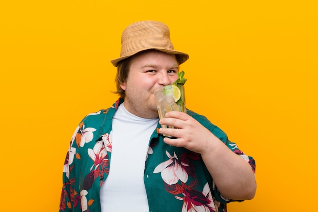 Young big size man with a mojito drink against flat wall