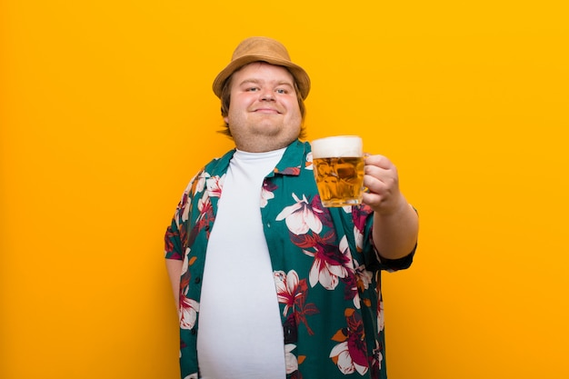 Young big size man with a pint of beer against flat wall
