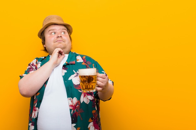 Young big size man with a pint of beer