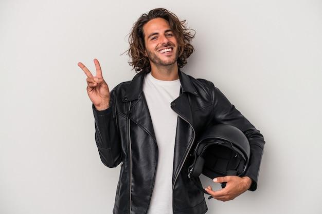灰色の背景に分離されたバイクのヘルメットを持っている若いバイカー白人男性は、指で平和のシンボルを示して楽しくてのんきです。