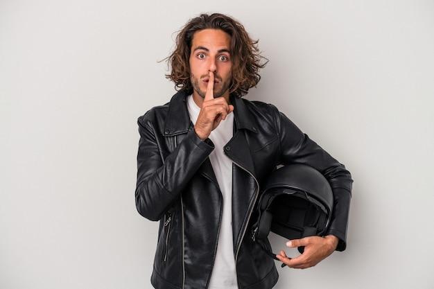 秘密を保持するか、沈黙を求めて灰色の背景に分離されたバイクのヘルメットを保持している若いバイカー白人男性。