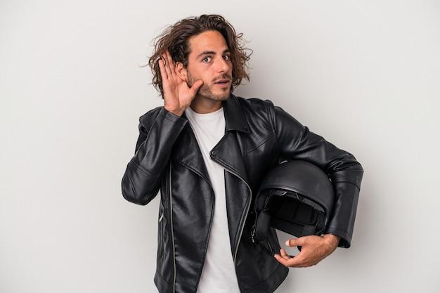 험담을 들으려고 노력하는 회색 배경에 고립 오토바이 헬멧을 들고 젊은 바이커 백인 남자.