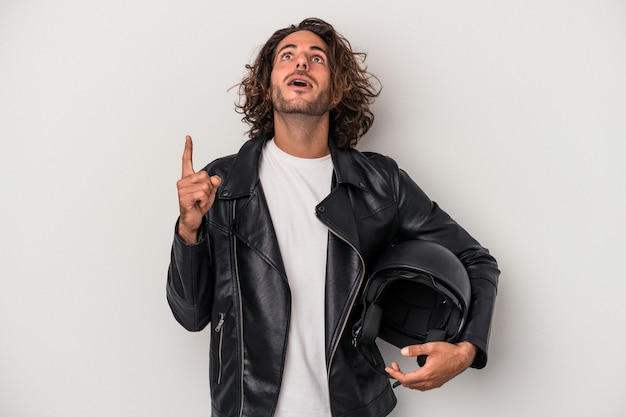 Young biker caucasian man holding a motorbike helmet isolated on gray background pointing upside with opened mouth.