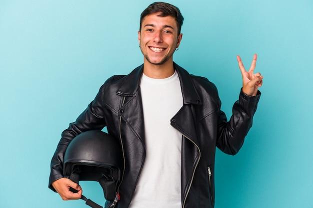 Молодой байкер мужчина держит шлем, изолированные на синем фоне, радостный и беззаботный, показывая пальцами символ мира.