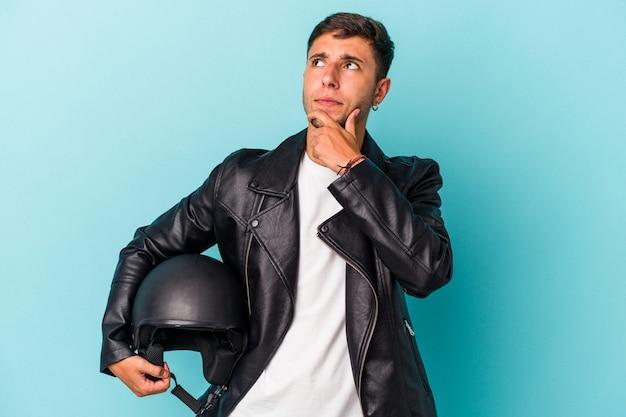 Молодой байкер мужчина держит шлем, изолированные на синем фоне, глядя в сторону с сомнительным и скептическим выражением лица.