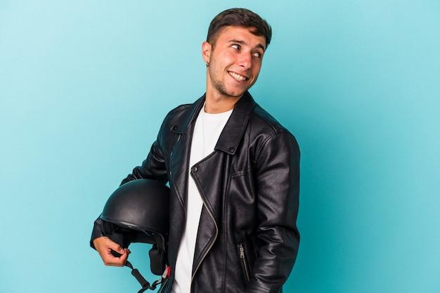 青い背景で隔離のヘルメットを保持している若いバイカーの男は、笑顔、陽気で楽しい脇に見えます。