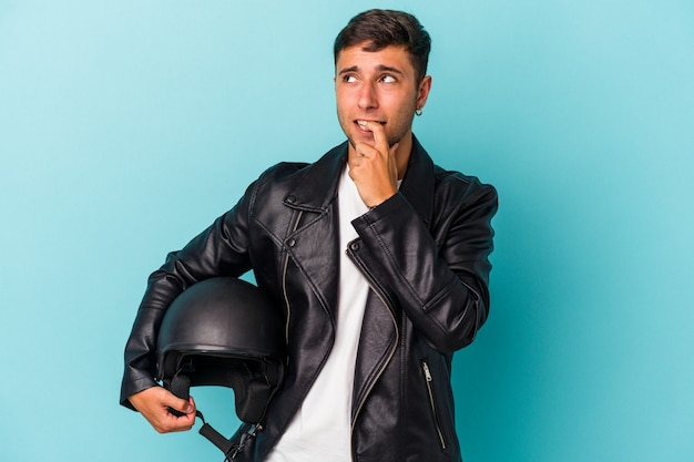 青い背景に分離されたヘルメットを保持している若いバイカーの男は、コピースペースを見ている何かについて考えてリラックスしました。
