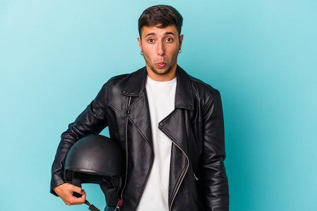 青い背景に分離されたヘルメットを保持している若いバイカーの男は、肩をすくめ、目を開いて混乱します。