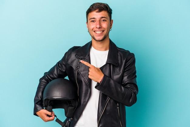 青い背景に分離されたヘルメットを保持している若いバイカーの男は、笑顔で脇を指して、空白のスペースで何かを示しています。