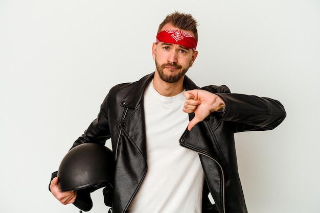 Молодой байкер татуированный кавказский мужчина, держащий шлем, изолированный на белом фоне, показывает жест неприязни, пальцы вниз. концепция несогласия.