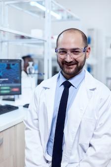 Молодой ученый-биохимик в защитных очках, улыбаясь в камеру. серьезный эксперт в области генетики в лаборатории с современными технологиями для медицинских исследований с африканским ассистентом на заднем плане.