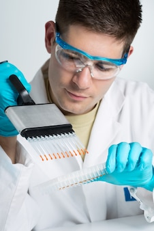 Young biologist with multichannel pipette
