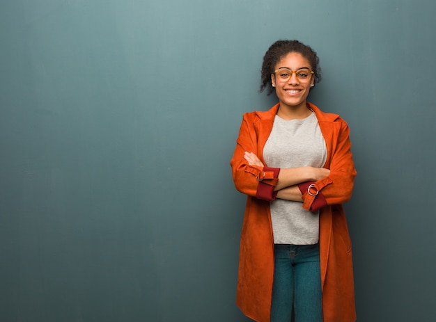 Young black african american girl with blue eyes crossing arms, smiling and relaxed