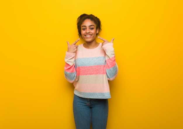 Young black african american girl with blue eyes smiles, pointing mouth