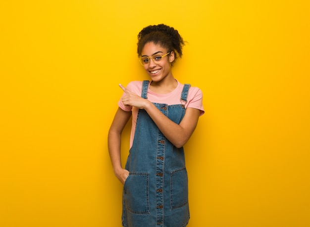 Young black african american girl with blue eyes smiling and pointing to the side