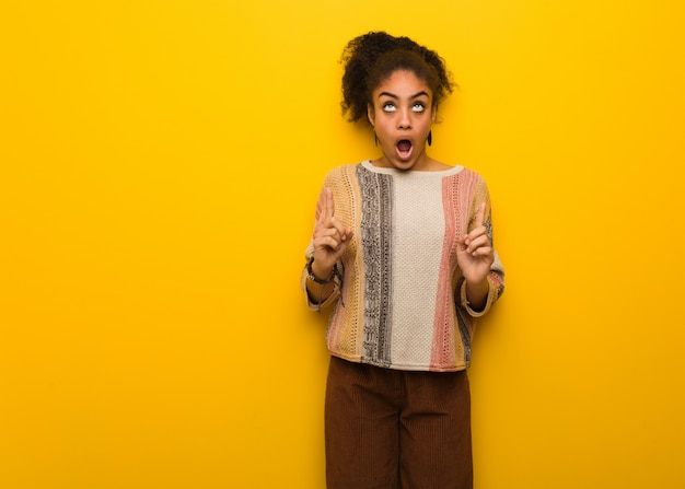 Young black african american girl with blue eyes surprised pointing up to show something