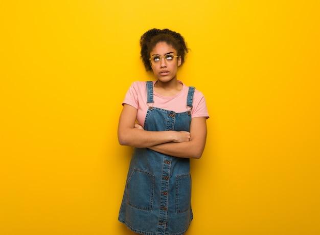Молодая черная афро-американская девушка с голубыми глазами устала и скучает
