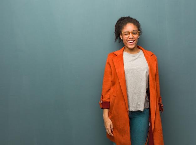 まばたき、面白い、フレンドリーで屈託のないジェスチャーで青い目の若い黒人アフリカ系アメリカ人の女の子