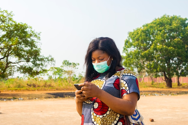 Young black african female business woman wearing face mask checking internet.