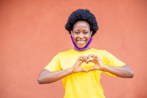 コロナウイルスパンデミックcovid19で彼女の鼻の下に保護布のフェイスマスクを身に着けている若い黒人アフリカの女の子