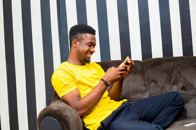 젊은 흑인 남성 힙스터는 소셜 네트워크에서 친구들과 채팅하고 집에 앉아 있는 동안 모바일 장치를 사용하여 온라인 뉴스를 읽습니다.